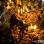 Janitzio Cemetery on Day of the Dead by Jesús Rosas. A picture of a woman next to a grave with bright yellow flowers and candles at night.