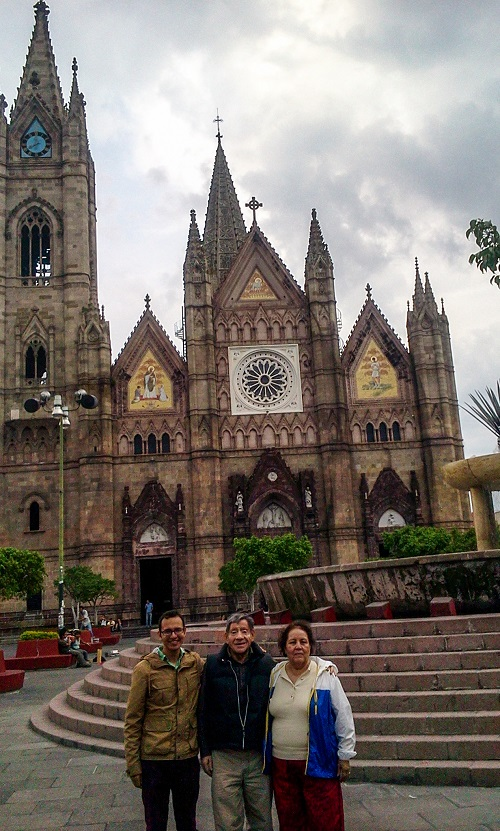 A picture of me and an older couple posing in front of a Catholic church with Neo-Gothic architecture.