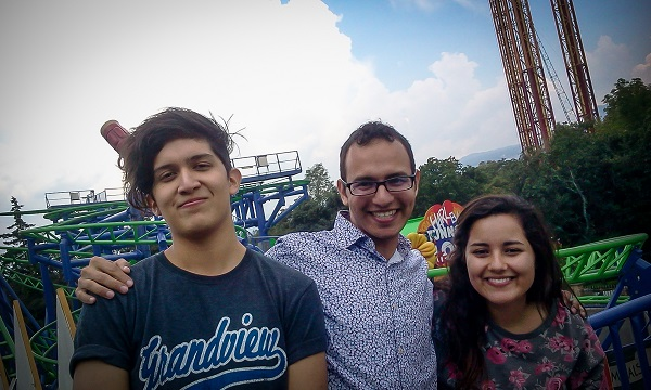 Picture of three people (me included) and in the back some roller-coaster tracks.