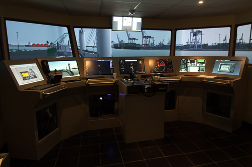 A picture of a maritime simulator with projections on the background as if there were a real maritime environment.