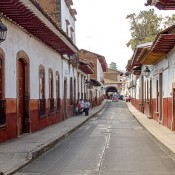 Picture of a street with houses on both sides of the street. Houses painted in white and red.