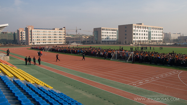 track and field with several hundred of students and five buildings on the background