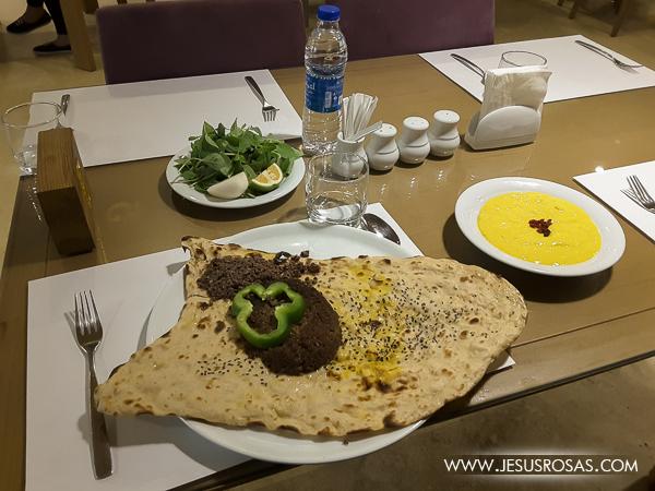 Carne molida de cordero con especias iranís acompañada de pan y hojas de albahaca y limón.