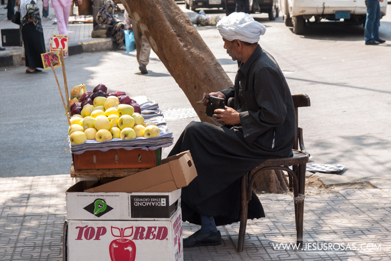 It is also common to find in the streets of Cairo many vendors. In this picture you can see a street vendor selling apples. He is wearing a galabiya, the traditional Egyptian robe and a turban. Cairo, Egypt. 2009.