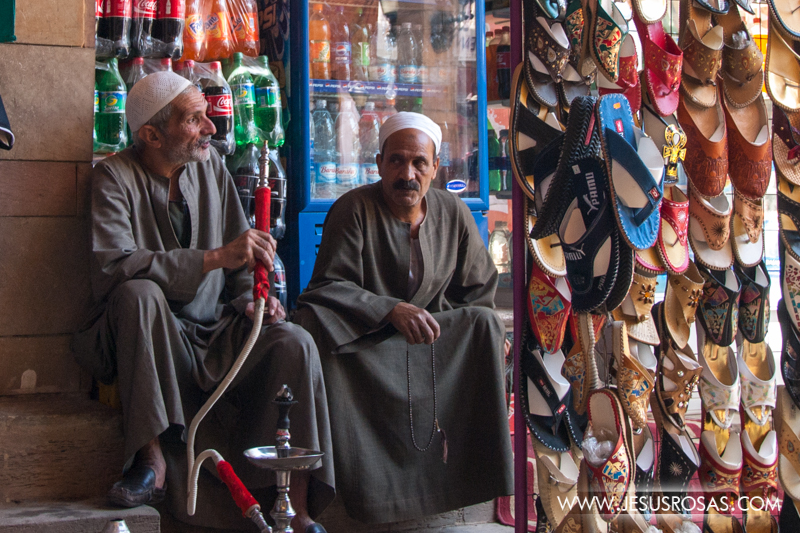 In this picture two men wearing their galabiya (traditional Egyptian cloak) and a white taqiyah (rounded cap). The man at the right holds the hose of an arghila (also known as hookah or shisha). The arghila is a popular smoking artifact in the Middle East. On the right side, traditional sandals. In the background, as in all the world, Coke-Cola. Luxor, Egypt 2009.