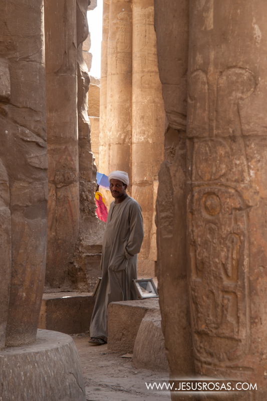 A man peep out between some pillars at the ancient Luxor Temple. Some of these men around the Luxor temple are unemployed men looking for tips from tourists, especially when they are photographed :) Luxor, Egypt. 2009.