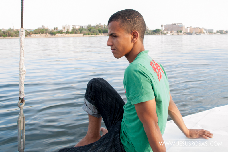 A young man in charge of a boat in the Nile River. His outfit is an example of an increasing Western trend among the younger generation. Luxor, Egypt. 2009.