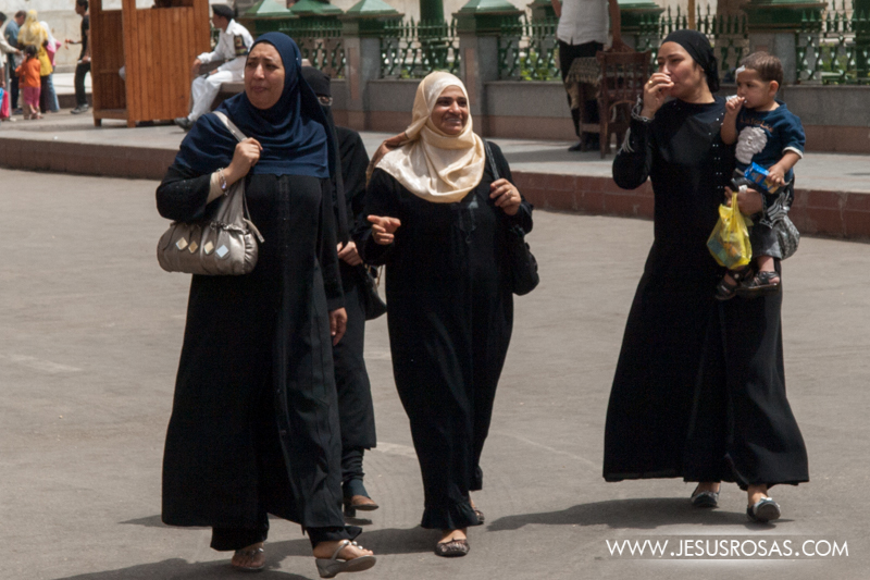 Muslim women crossing a street. Each is wearing a hijab on the head and an abaya (robe-like dress). Cairo, Egypt. 2009.
