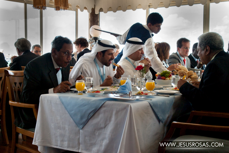 Saudis (from Saudi Arabia) in Alexandria at a restaurant eating with some Westerners and possibly some locals. Saudis and some other Arabs in the Arabian Peninsula are characterized by their white kufiya (a headdress worn by men) tied with an agal (black cord to keep the kufiya on the wearer's head) and a white cloak, similar to the galabiya (see above), but called thawb. Alexandria, Egypt. 2009.