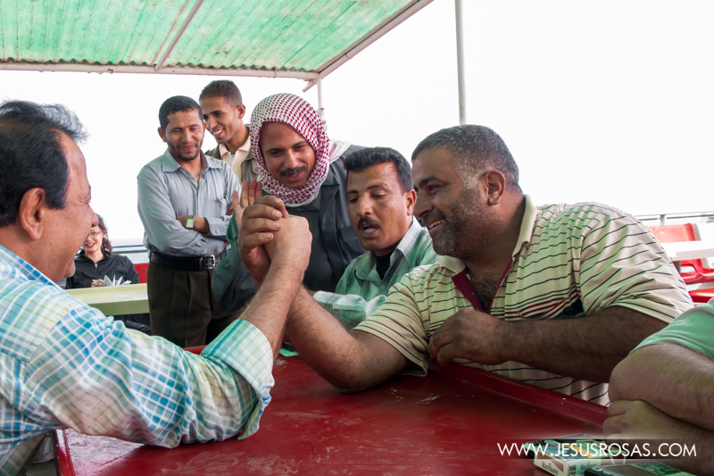 Arab passengers playing arm wrestling during a trip crossing the Red Sea on a ferry from Nuweiba, Egypt to Aqaba, Jordan. Nuweiba, Egypt. 2009.