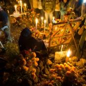 Janitzio en el día de los muertos. Mujer en cementerio o panetón a un lado de una tumba decorada con velas y flores amarillas y anaranjadas llamadas xempazúchitl. Michoacán, México. Foto tomada por Jesús Rosas.