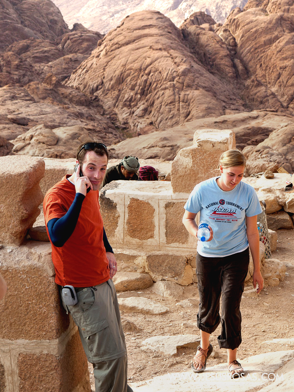Student wearing orange t-shirt and gray pants with a cellphone on top of Mount Sinai. Girl with a bottle of water passing next to him.