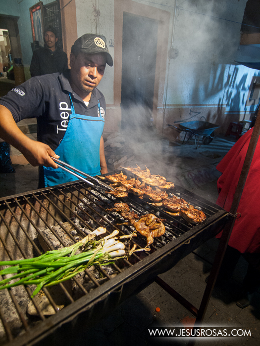 Image of a man grilling several quails and some onions in Cajititlan, Tlajomulco, Jalisco, Mexico.