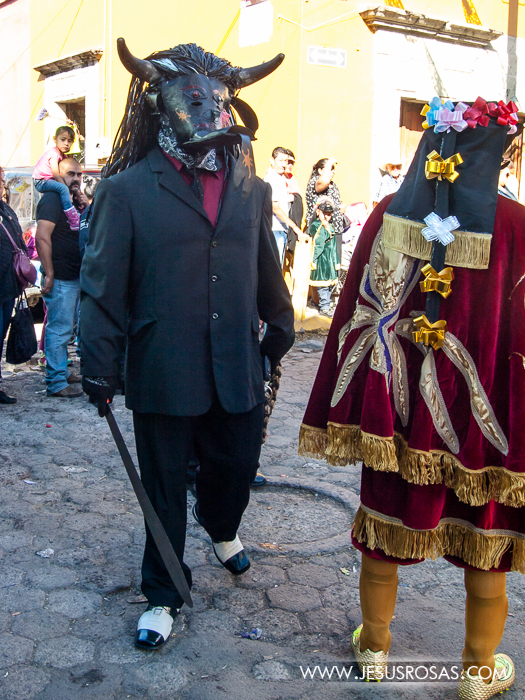 "Two men wearing masks and outfits representing the ""morenos"" during the procession in Cajititlan, Tlajomulco, Jalisco, Mexico."