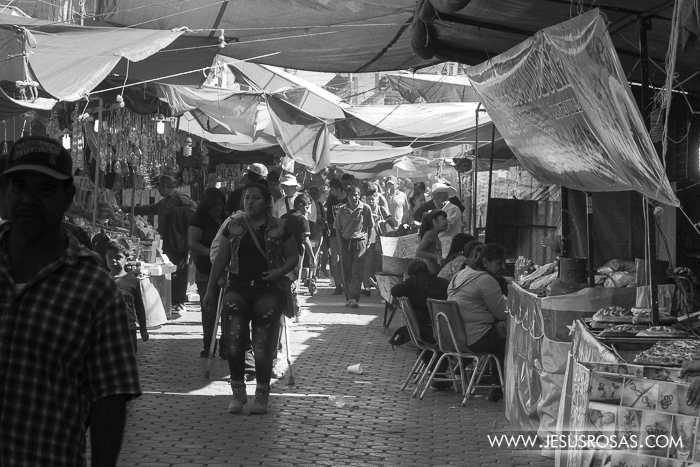 Black and white picture of people walking on a street full of stands in Cajititlan, Jalisco, Mexico.