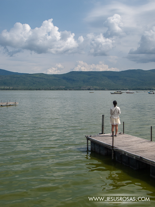 A woman standing on a deck while looking at the lake, mountains and clouds in Cajititlan, Tlajomulco, Jalisco, Mexico.