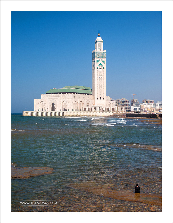 A woman admiring the mosque from the water.