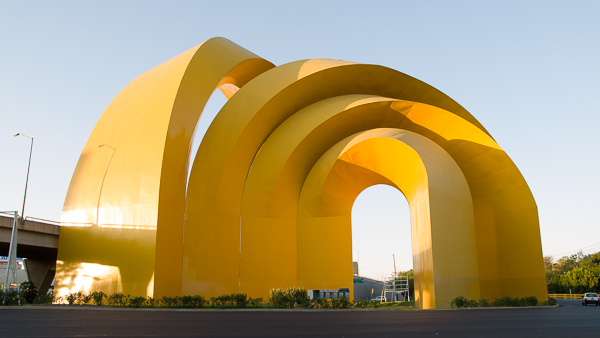 Image of a big monument composed of yellow arches in Guadalajara.