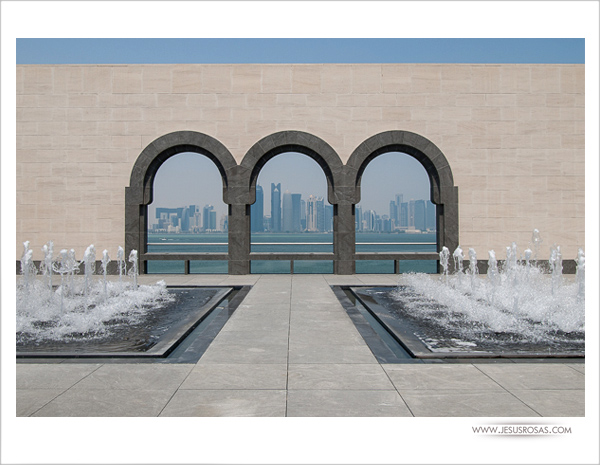 Patio with fountains and three arches, beyond the arches Doha skyline can be seen.
