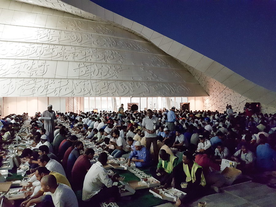 Muslim workers gathered outside the mosque to break their fast. Doha, Qatar.