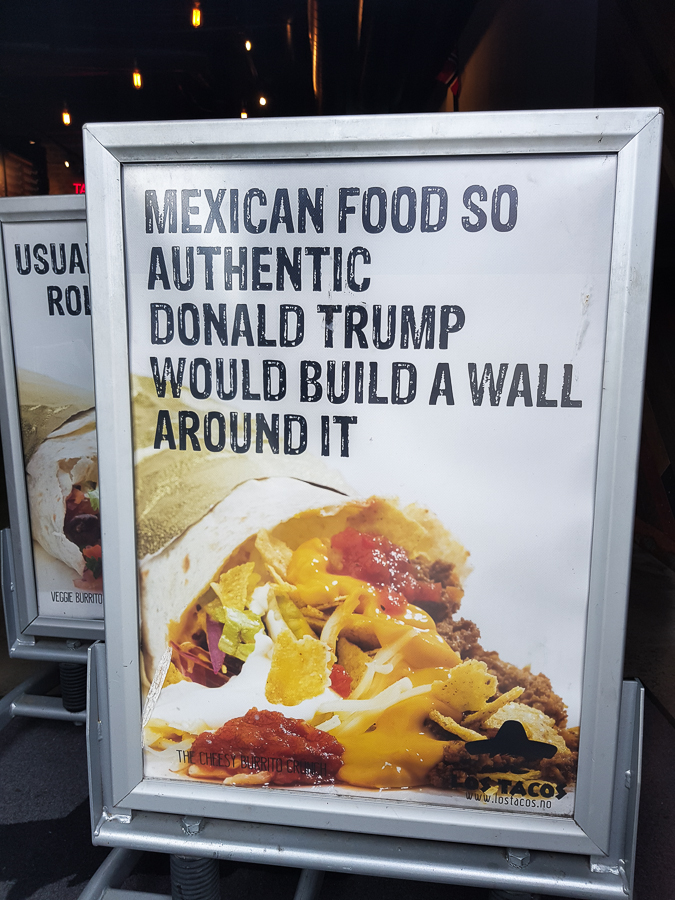 Picture of a sign outside a restaurant. The sign shows a burrito or taco and it reads 'Mexican food so authentic Donald Trump would build a wall around it.